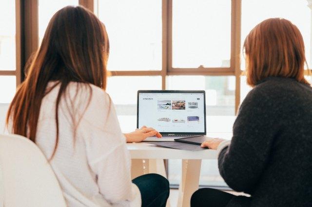 Two women sitting at laptop